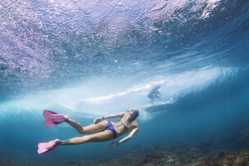 a blonde gorgeous lady swimming with pink swim fins surf banyak