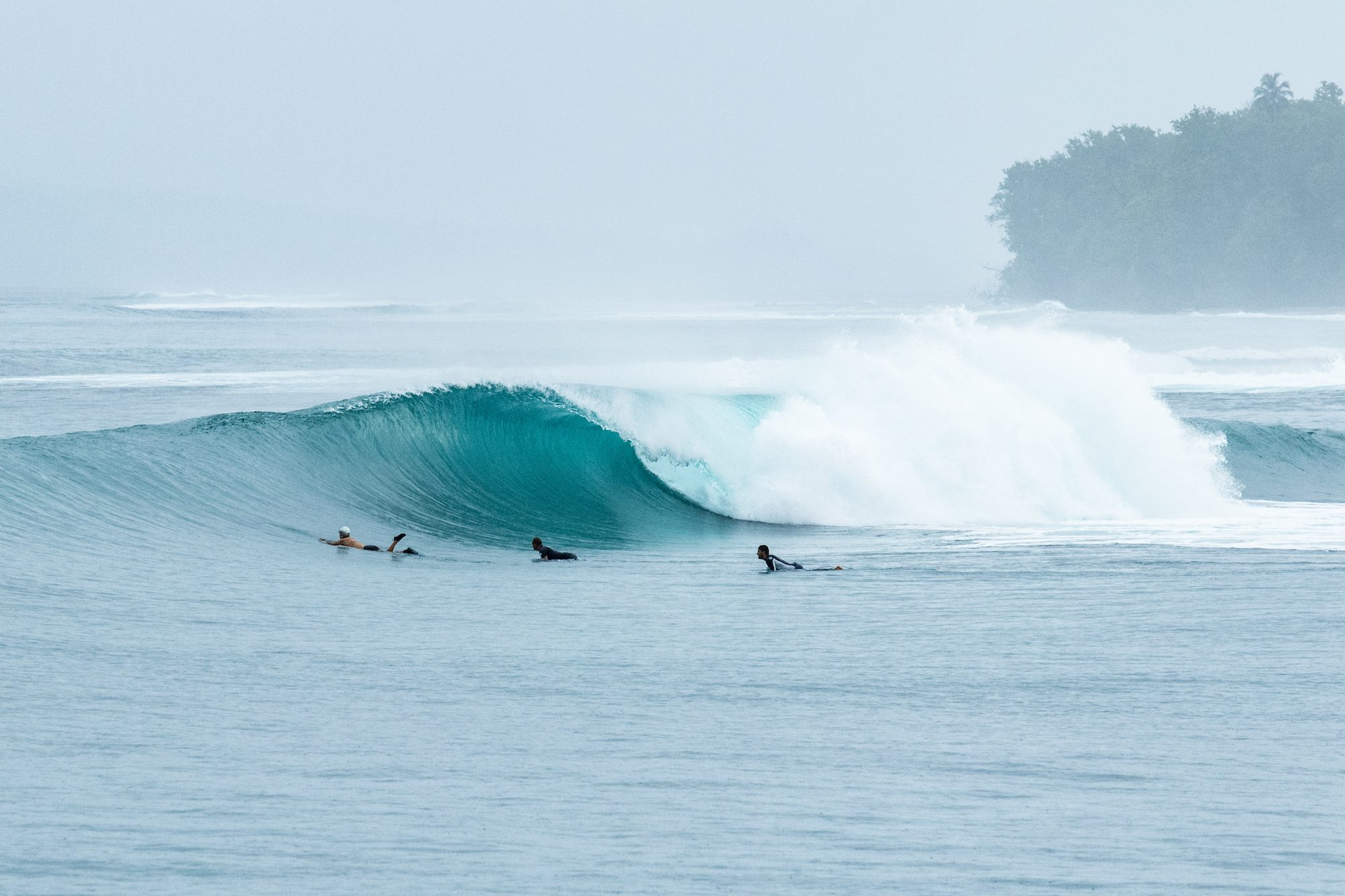 spilling wave with some surfers on the side, surf banyak