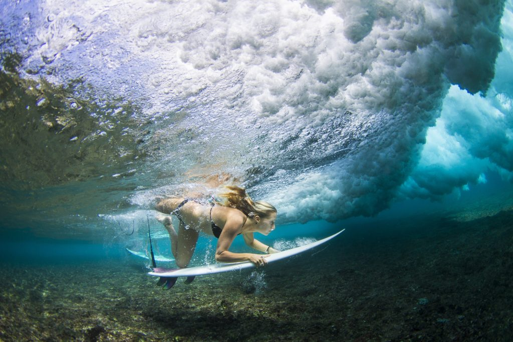 a girl doing a amazing duck diving by surf banyak